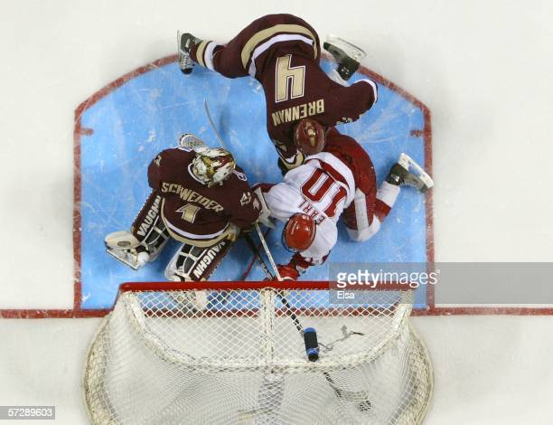 Robbie Earl of Wisconsin gets the puck past Cory Schneider of Boston College as teammate Mike Brennan looks on during the NCAA Men's Frozen Four...