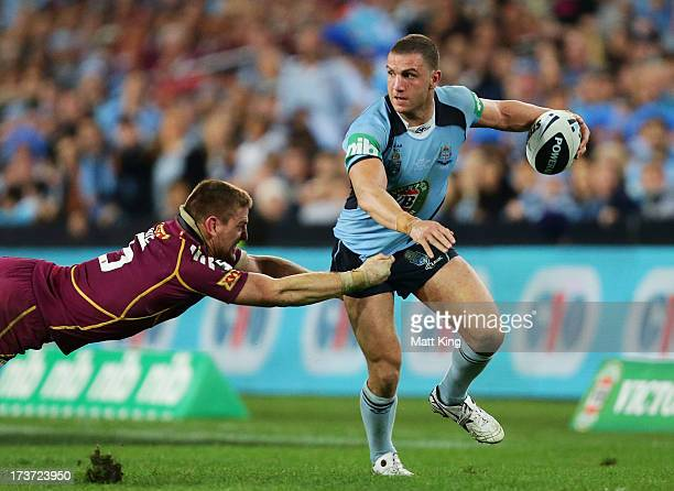 Robbie Farah of the Blues is tackled by Brent Tate of the Maroons during game three of the ARL State of Origin series between the New South Wales...