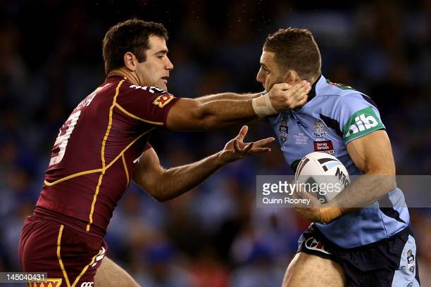 Robbie Farah of the Blues is tackled by Cameron Smith of the Maroons during game one of the ARL State of Origin series between the Queensland Maroons...