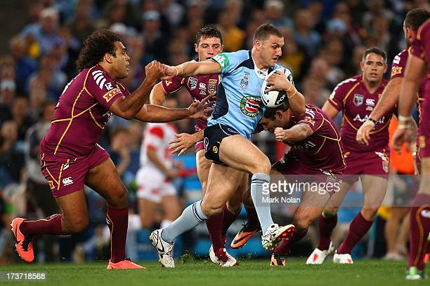 Robbie Farah of the Blues is tackled during game three of the ARL State of Origin series between the New South Wales Blues and the Queensland Maroons...