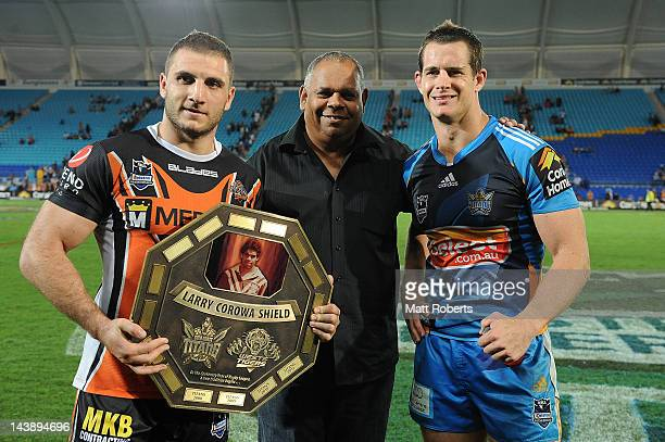 Robbie Farah of the Tigers and Ashley Harrison of the Titans poses with Larry Corowa after the round nine NRL match between the Gold Coast Titans and...