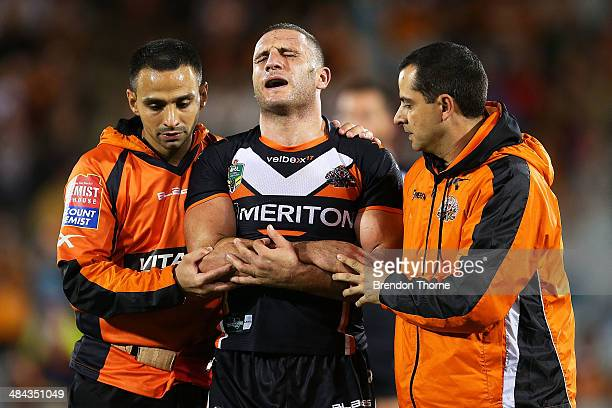 Robbie Farah of the Tigers is helped from the field after sustaining an injury to his elbow during the round 6 NRL match between the Wests Tigers and...