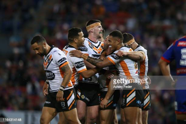 Robbie Farah of the Wests Tigers celebrates his try with team mates during the round 19 NRL match between the Newcastle Knights and Wests Tigers at...
