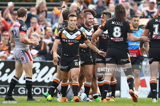 Robbie Farah of the Wests Tigers celebrates with his team mates after scoring a try during the round 25 NRL match between the Wests Tigers and the...