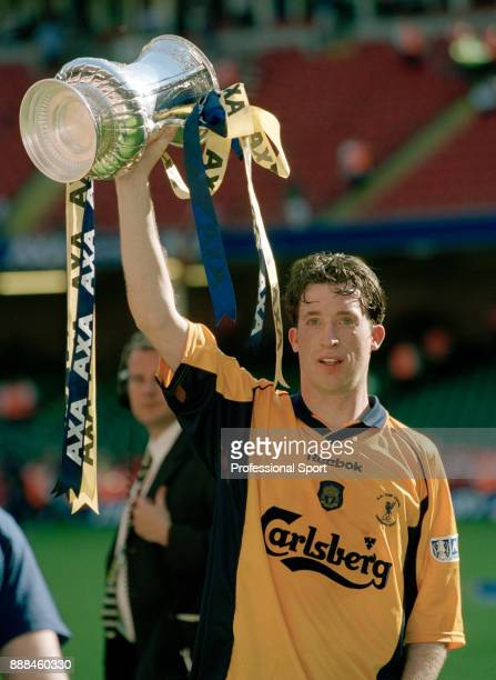 Robbie Fowler of Liverpool celebrates with the FA Cup after their victory over Arsenal in the FA Cup Final at the Millenium Stadium on May 12 2001 in...