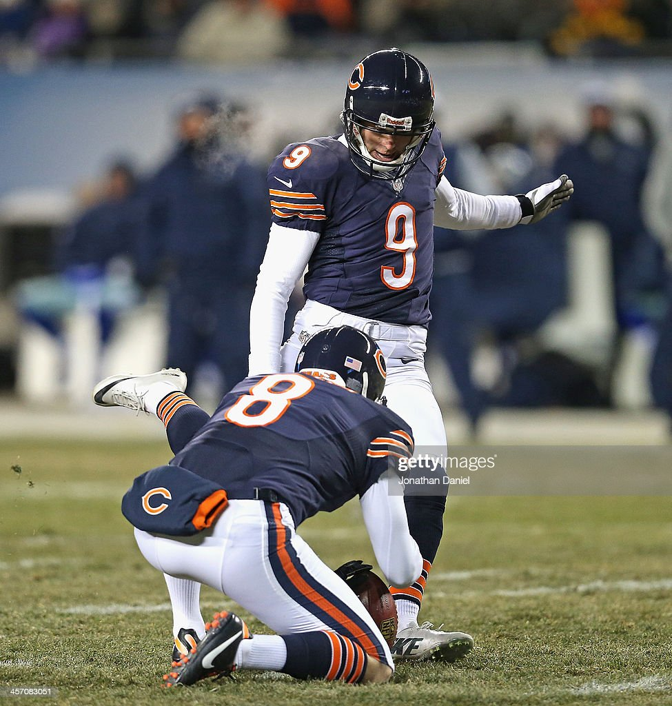 Robbie Gould #9 of the Chicago Bears kicks a field goal out of the hold of Adam Podlesh #8 against the Dallas Cowboys at Soldier Field on December 9, 2013 in Chicago, Illinois. The Bears defeated the Cowboys 45-28.