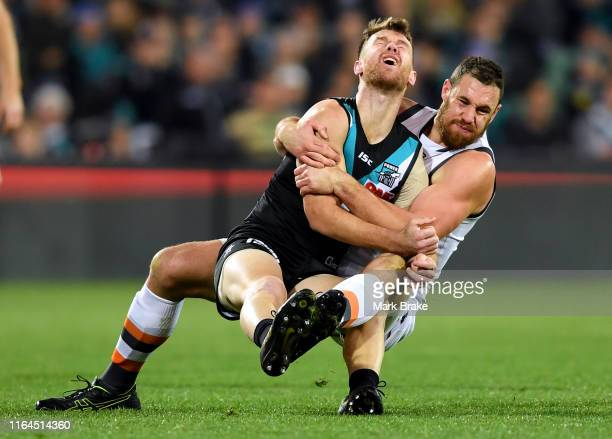 Robbie Gray of Port Adelaide gets tackled without he ball by Shane Mumford of the Giants during the round 19 AFL match between the Port Adelaide...