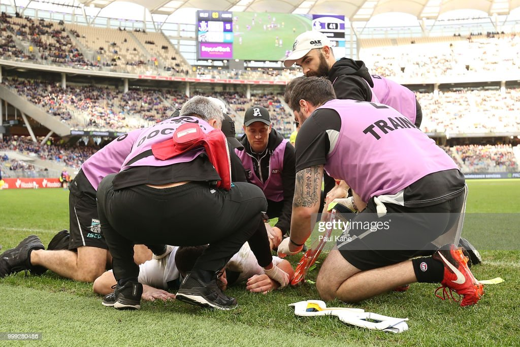 Robbie Gray of the Power is attended to by medical staff after being tackled by Ryan Nyhuis of the Dockers during the round 17 AFL match between the Fremantle Dockers and the Port Adelaide Power at Optus Stadium on July 15, 2018 in Perth, Australia.