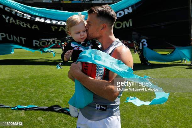 Robbie Gray of the Power runs through the banner with son Aston before his 200th match during the 2019 AFL round 01 match between the Melbourne...