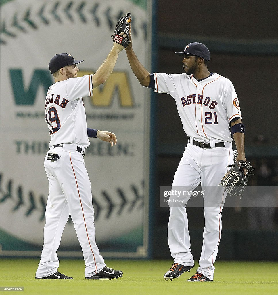 Robbie Grossman #19 and Dexter Fowler #21 of the Houston Astros high five after the final out as Houston wins 4-2 ocer the Oakland Athletics at Minute Maid Park on August 26, 2014 in Houston, Texas.