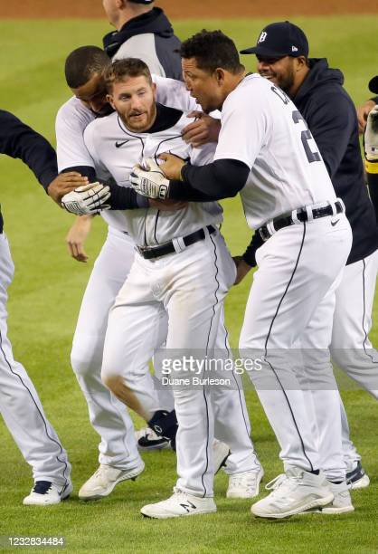Robbie Grossman of the Detroit Tigers celebrates with Nomar Mazara and Miguel Cabrera after hitting a walk-off single to defeat the Kansas City...