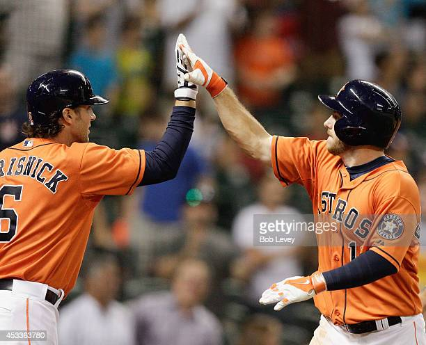 Robbie Grossman of the Houston Astros high fives his teammate Jake Marisnick after hitting a home run in the eighth inning against the Texas Rangers...