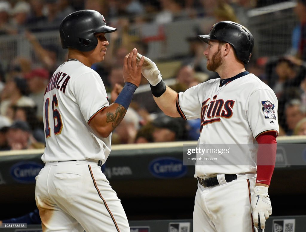 Robbie Grossman #36 of the Minnesota Twins congratulates teammate Ehire Adrianza #16 on scoring a run against the New York Yankees during the fourth inning of the game on September 11, 2018 at Target Field in Minneapolis, Minnesota. The Twins defeated the Yankees 10-5.