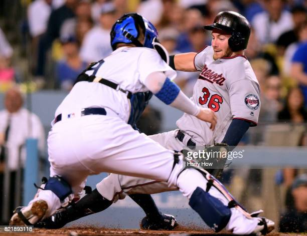Robbie Grossman of the Minnesota Twins is tagged out by Yasmani Grandal of the Los Angeles Dodgers as he tries to score during the fourth inning at...