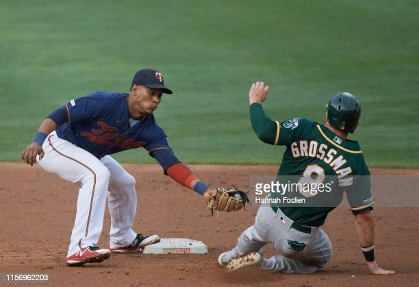 Robbie Grossman of the Oakland Athletics is out at second base as Jorge Polanco of the Minnesota Twins applies the tag to complete a double play...