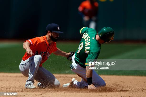 Robbie Grossman of the Oakland Athletics is tagged out attempting to steal second base by Jack Mayfield of the Houston Astros during the fourth...