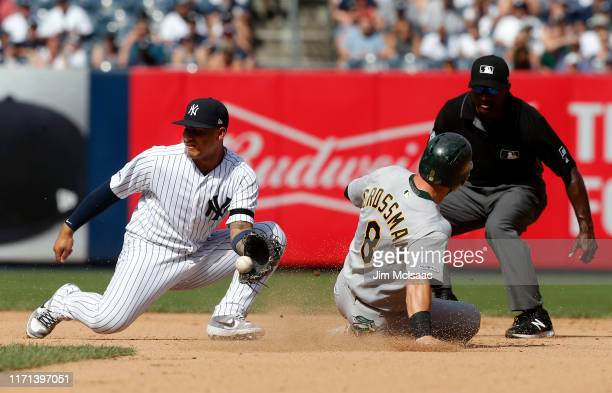 Robbie Grossman of the Oakland Athletics steals second base in the seventh inning ahead of the tag from Gleyber Torres of the New York Yankees at...