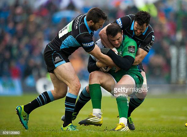 Robbie Henshaw of Connacht tackled by Tommy Seymour and Simone Favaro of Glasgow during the Guinness PRO12 rugby match between Connacht Rugby and...