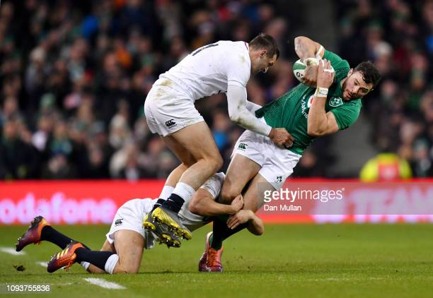 Robbie Henshaw of Ireland is tackled by Ben Youngs and Jonny May of England during the Guinness Six Nations between Ireland and England at Aviva...