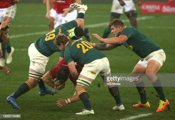 Robbie Henshaw of the British & Irish Lions is tackled by Marco van Staden and Kwagga Smith of South Africa during the 3rd Test between South Africa...