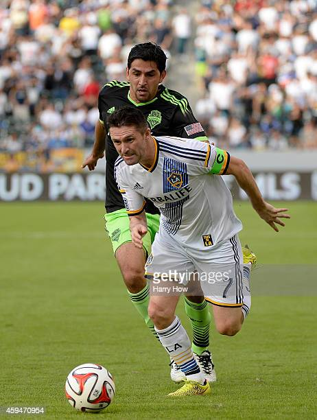 Robbie Keane of Los Angeles Galaxy dribble around Leo Gonzalez of Seattle Sounders FC during the Western Conference Final at StubHub Center on...