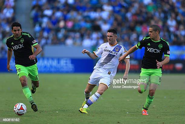 Robbie Keane of Los Angeles Galaxy passes the ball between Leo Gonzalez and Osvaldo Alonso of Seattle Sounders FC during the MLS match at StubHub...