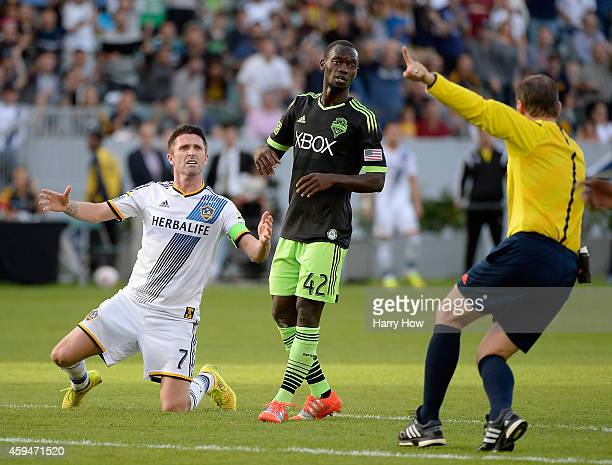 Robbie Keane of Los Angeles Galaxy reacts to a foul in front of the referee Kevin Scott and Micheal Azira of Seattle Sounders FC during the Western...