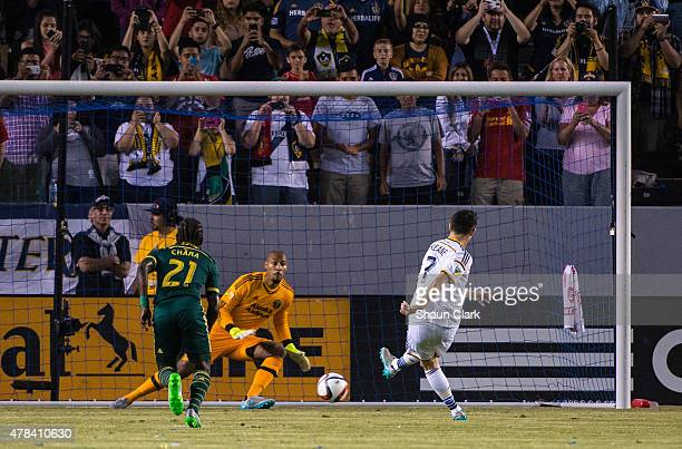 Robbie Keane of Los Angeles Galaxy scores on a penalty kick as Adam Kwarasey of Portland Timbers goes the wrong direction during Los Angeles Galaxy's...
