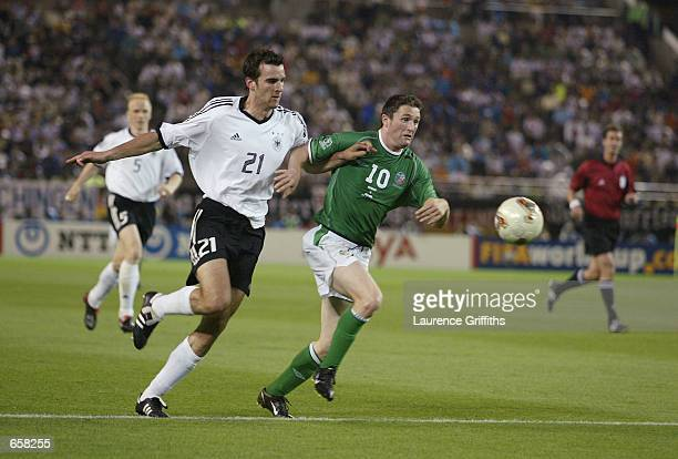 Robbie Keane of Republic of Ireland and Christoph Metzelder of Germany battle for the ball during the Group E match of the World Cup Group Stage...