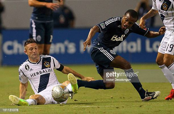 Robbie Keane of the Los Angeles Galaxy and Dane Richards of the Vancouver Whitecaps vie for the ball in the first half during the MLS match at The...