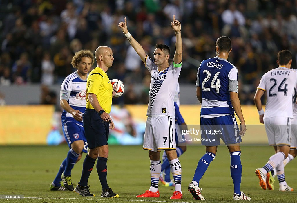 Robbie Keane #7 of the Los Angeles Galaxy celebrates his first half goal against FC Dallas as referee Allen Chapman, Stephen Keel #22 and Matt Hedges #24 of FC Dallas look on during the MLS match at StubHub Center on May 21, 2014 in Los Angeles, California. The Galaxy defeated FC Dallas 2-1.