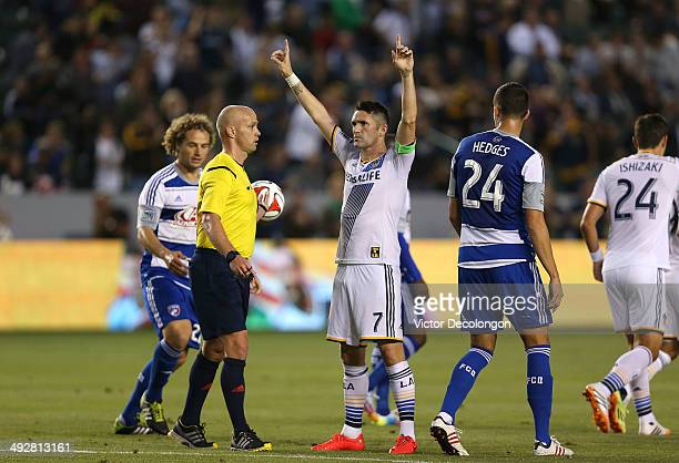 Robbie Keane of the Los Angeles Galaxy celebrates his first half goal against FC Dallas as referee Allen Chapman Stephen Keel and Matt Hedges of FC...