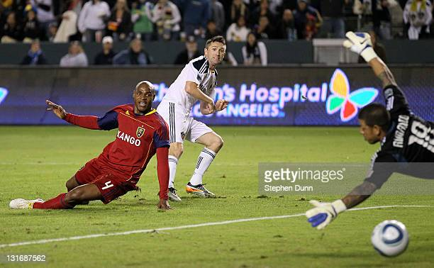 Robbie Keane of the Los Angeles Galaxy gets a shot past Jamison Olave and goal keeper Nick Rimando of Real Salt Lake to score the Galaxy's third goal...