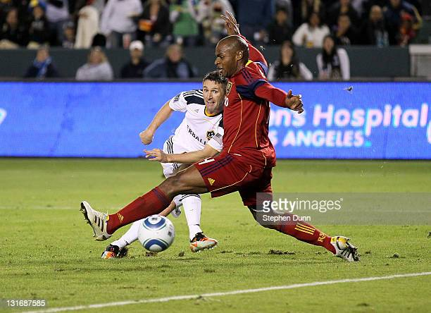 Robbie Keane of the Los Angeles Galaxy gets a shot past Jamison Olave of Real Salt Lake to score the Galaxy's third goal in the MLS Western...