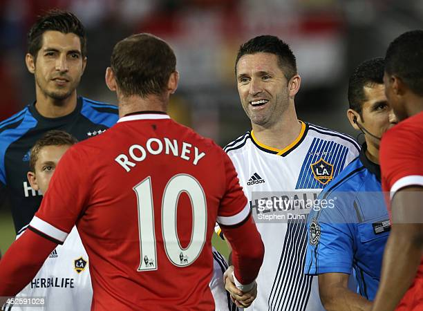 Robbie Keane of the Los Angeles Galaxy greets Wayne Rooney of Manchester United drurning prematch ceremonies at the Rose Bowl on July 23 2014 in...