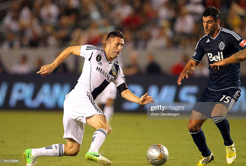 Robbie Keane #7 of the Los Angeles Galaxy plays the ball past Martin Bonjour #15 of the Vancouver Whitecaps during the MLS match at The Home Depot Center on September 1, 2012 in Carson, California. The Galaxy defeated the Whitecaps 2-0.