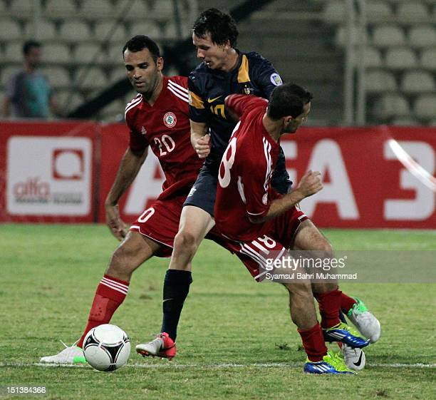 Robbie Kruse of Australia fights for the ball with Walid Ismail and Roda Antar of Lebanon during the International Friendly match between Lebanon and...
