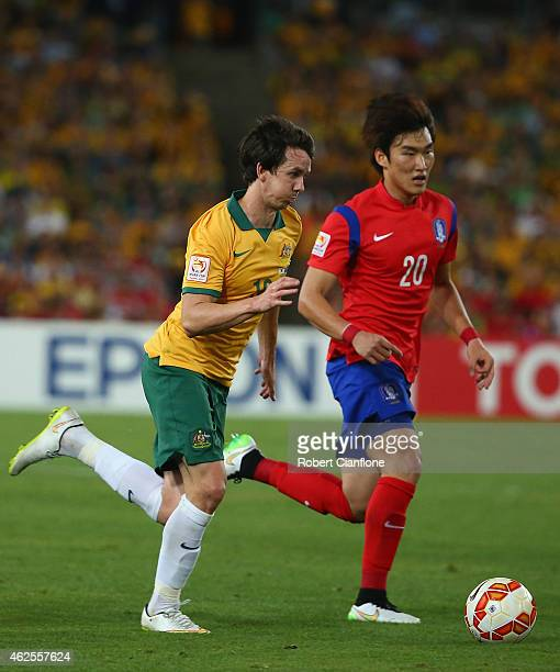Robbie Kruse of Australia is chased by Jang Hyunsoo of Korea Republic during the 2015 Asian Cup final match between Korea Republic and the Australian...
