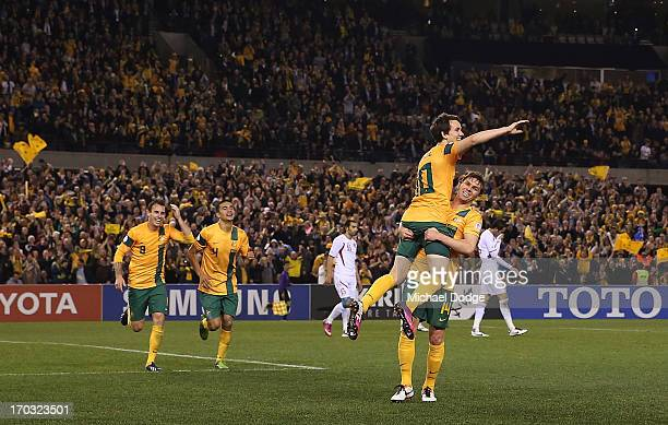 Robbie Kruse of the Socceroos gets lifted up by Brett Holman as he celebrates a goal during the FIFA World Cup Qualifier match between the Australian...