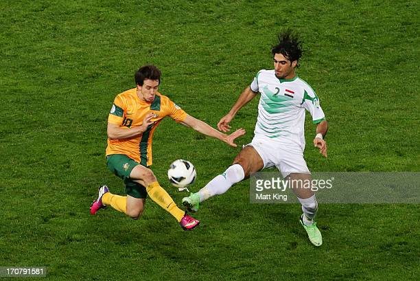 Robbie Kruse of the Socceroos is challenged by Ibrahim Ahmed of Iraq during the FIFA 2014 World Cup Asian Qualifier match between the Australian...
