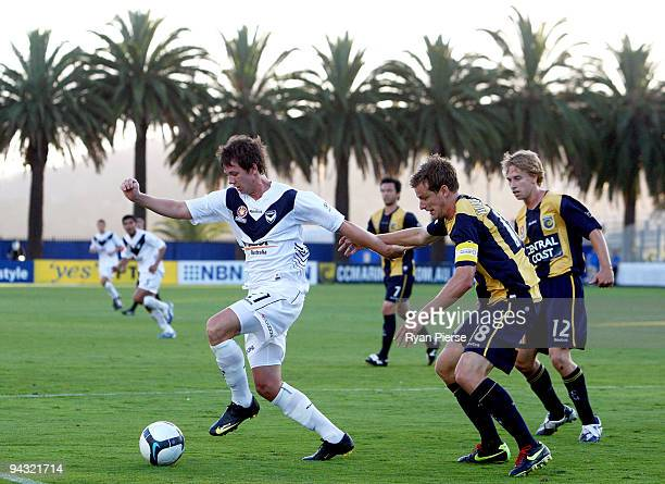 Robbie Kruse of the Victory is challenged by Alex Wilkinson of the Mariners during the round 18 A-League match between the Central Coast Mariners and...