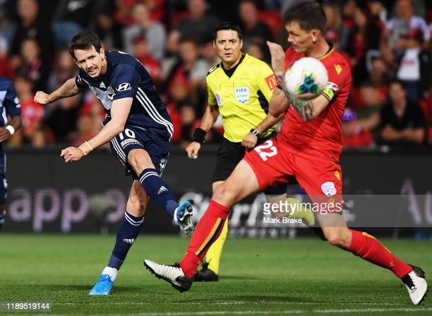Robbie Kruse of the Victory shoots for goal pass Michael Jakobson of Adelaide United during the round 7 ALeague match between Adelaide United and...