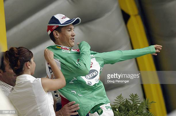 Robbie McEwen of Australia riding for LottoDomo puts on the green jersey following the individual time trial on stage 19 of the Tour de France from...