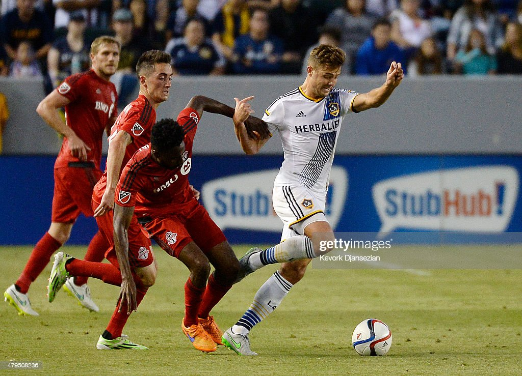 Robbie Rogers #14 of Los Angeles Galaxy is tackled by Warren Creavalle #3 of Toronto FC during the first half of their soccer match on July 4, 2015 at StubHub Center in Carson, California.