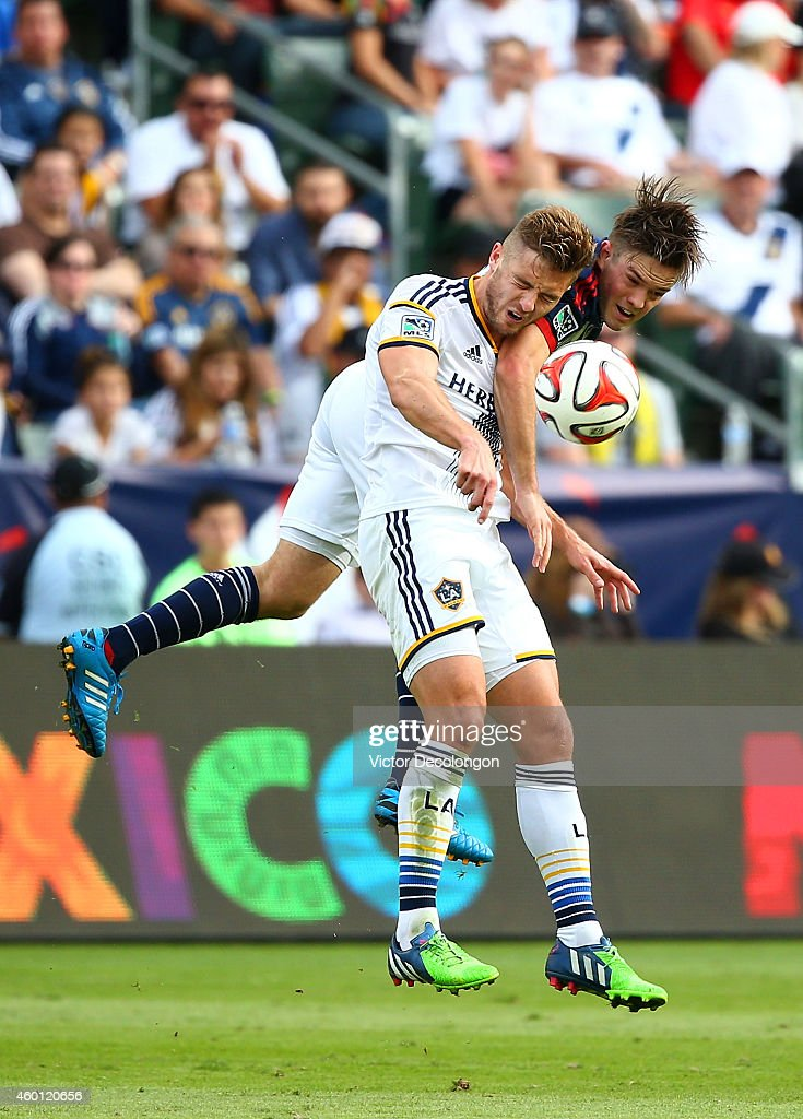 Robbie Rogers #14 of the Los Angeles Galaxy takes an elbow to the jaw from Kelyn Rowe #11 of the New England Revolution as they vie for the ball in the second half of regulation time during 2014 MLS Cup at StubHub Center on December 7, 2014 in Los Angeles, California. The Galaxy defeated the Revolution 2-1.