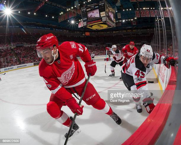 Robbie Russo and Tomas Nosek of the Detroit Red Wings battles along the boards with Ben Thomson and Miles Wood of the New Jersey Devils during the...