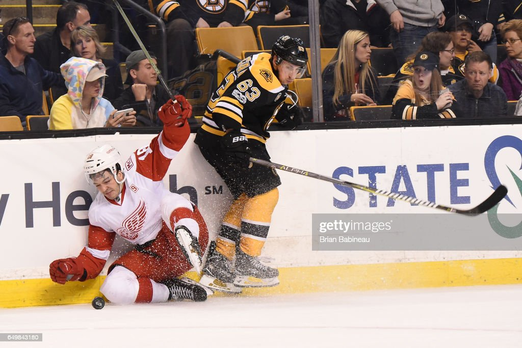 Robbie Russo #18 of the Detroit Red Wings fights for the puck against Brad Marchand #63 of the Boston Bruins at the TD Garden on March 8, 2017 in Boston, Massachusetts.