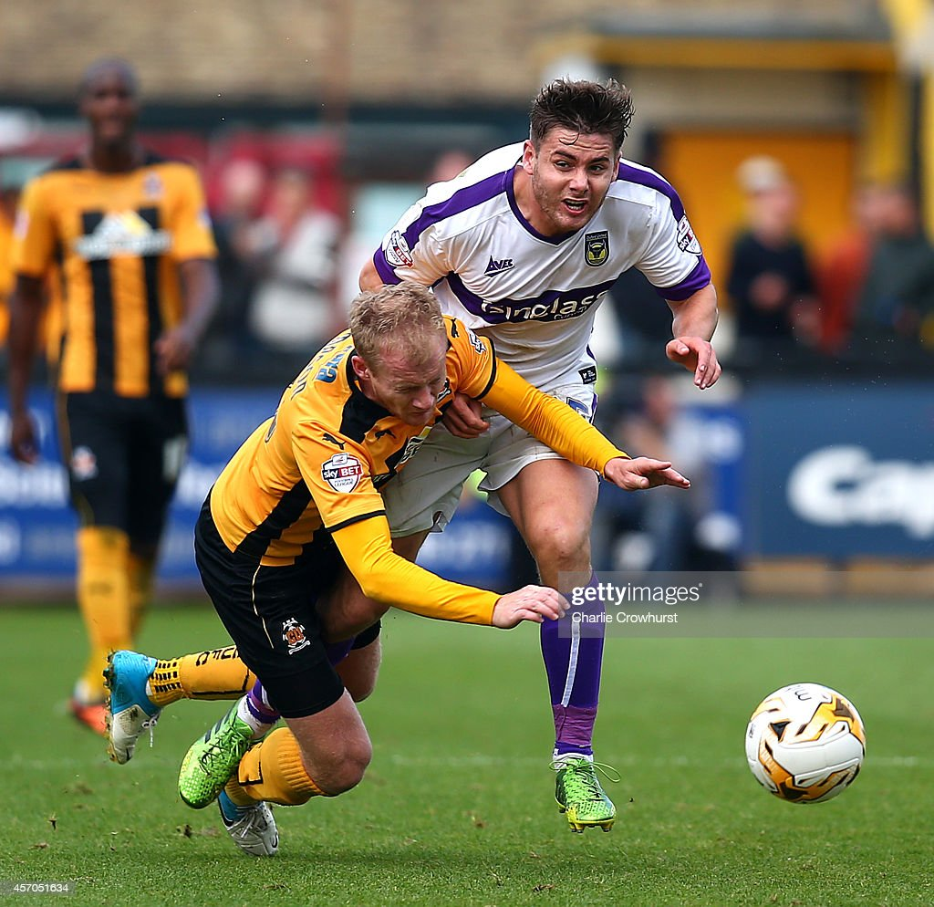 Robbie Simpson (L) of Cambridge clashes with Joe Riley of Oxford during the Sky Bet League Two match between Cambridge United and Oxford United at The Abbey Stadium on October 11, 2014 in Cambridge, England.