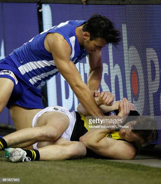 Robbie Tarrant of the Kangaroos and Jack Riewoldt of the Tigers clash during the 2017 AFL round 11 match between the North Melbourne Kangaroos and...