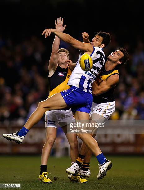 Robbie Tarrant of the Kangaroos competes with Matt White and Alex Rance of the Tigers during the round 15 AFL match between the North Melbourne...